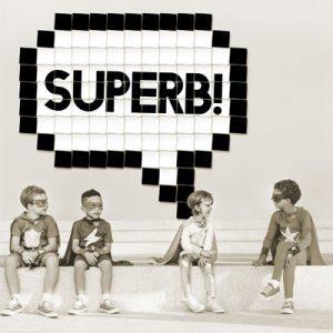 Vier als Superhelden verkleidete Kinder sitzen nebeneinander.
