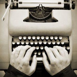 Zwei Hände tippen einen Text auf einer Schreibmaschine.