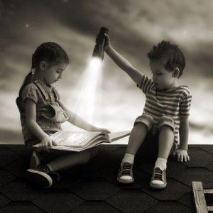 Zwei Kinder sitzen auf dem Dach und sehen sich ein Bilderbuch an.
